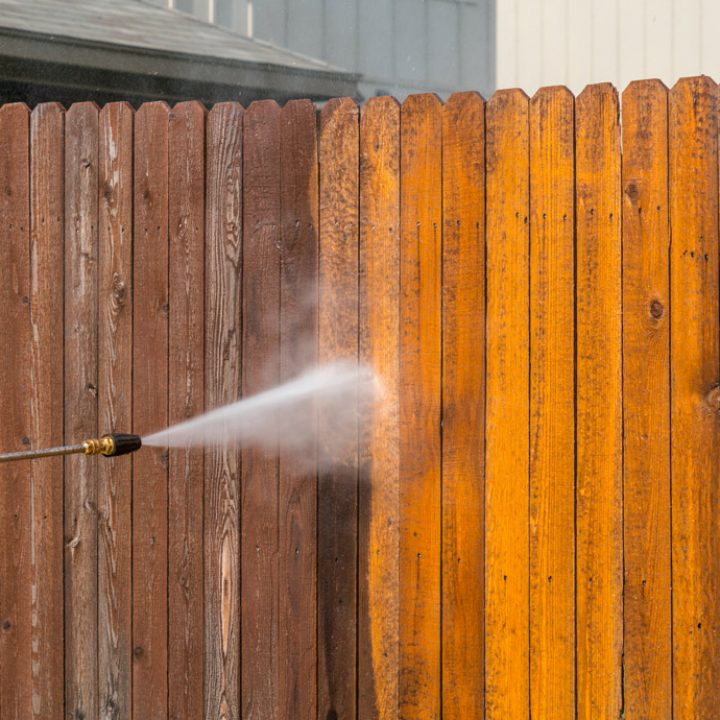 worker cleaning a wooden fence